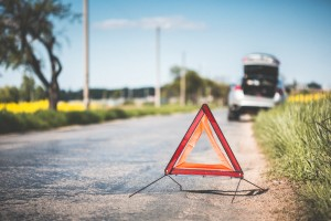 Les assurances indispensables de l'entrepreneur  red warning triangle and broken car at the side of the road picjumbo com 300x200